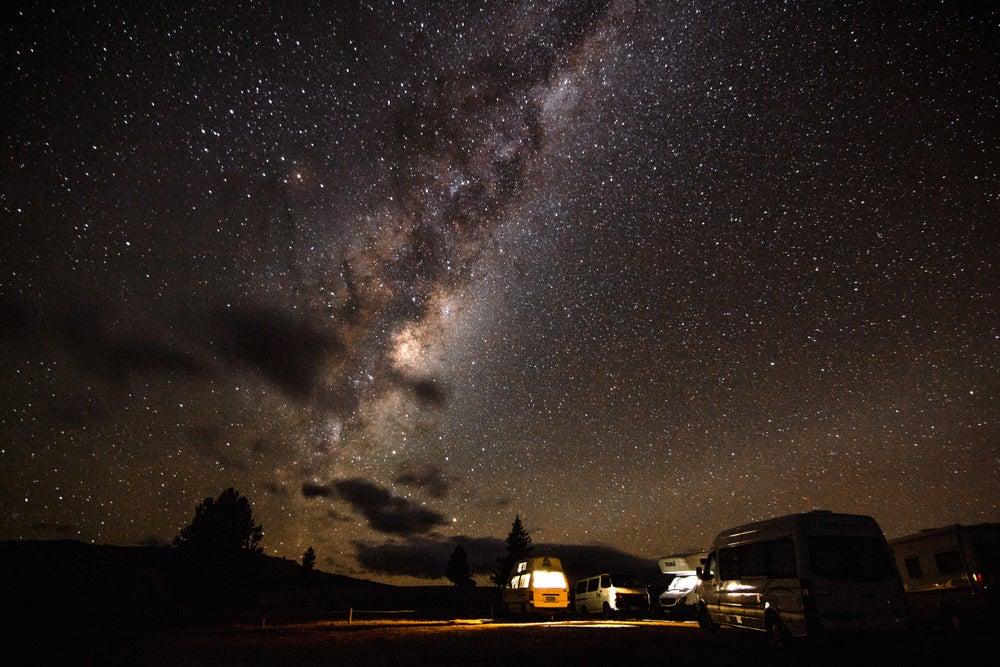 Long exposure of vans camped below the night sky, galaxies visible overhead.