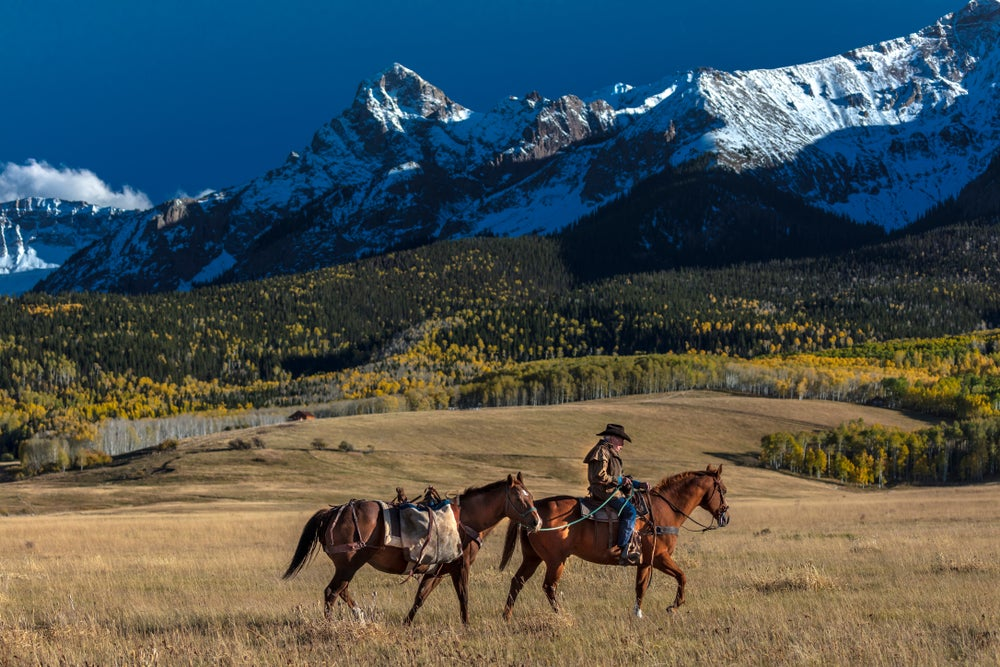 Rancher riding and leading a horse in the Colorado Rockies.