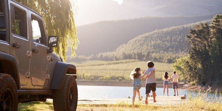 Mountainous scene with jeep in corner and family running to lake
