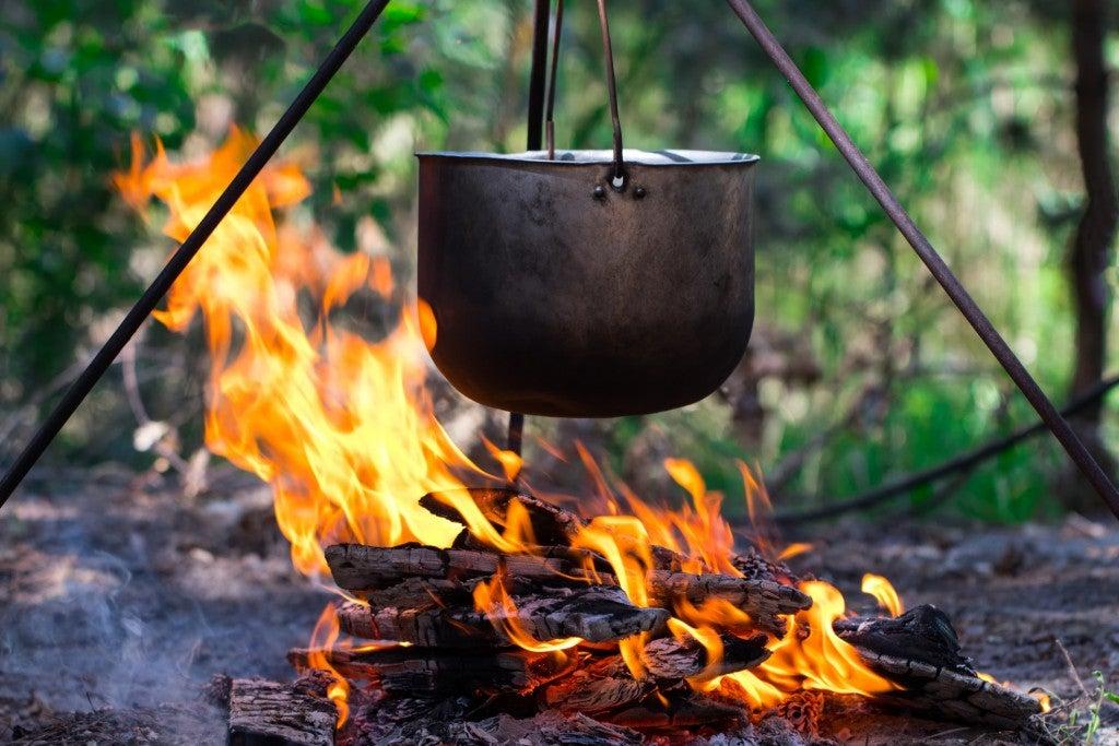 metal pot hanging over campfire