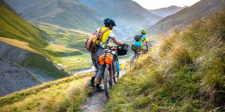 Bike packers walking their bikes on a dirt road through a field.