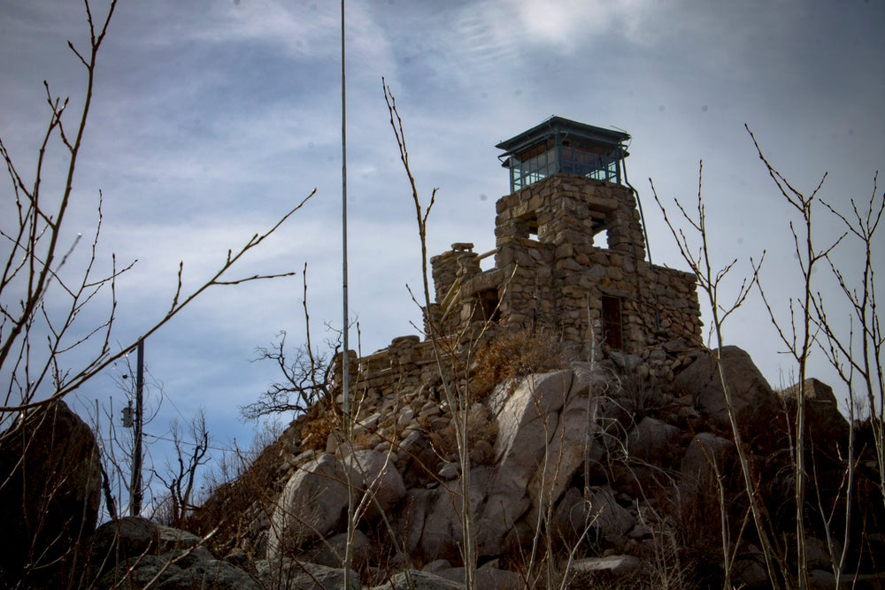 Bare trees frame a stone fire tower on rocky hill