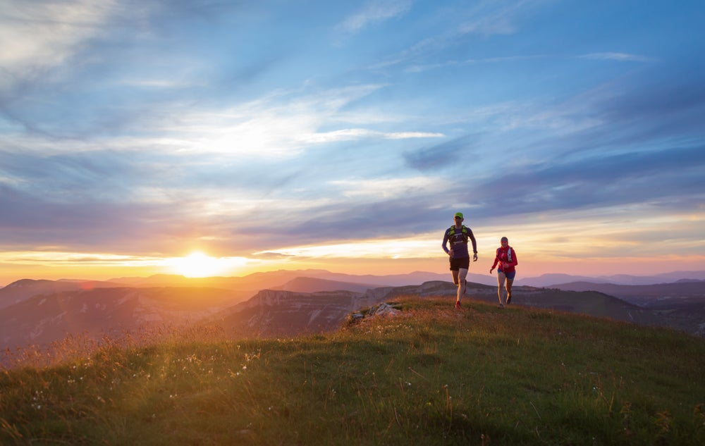 Two trail runners running on a grassy peninsula at sunset, with mountain ranges visible in the distance.