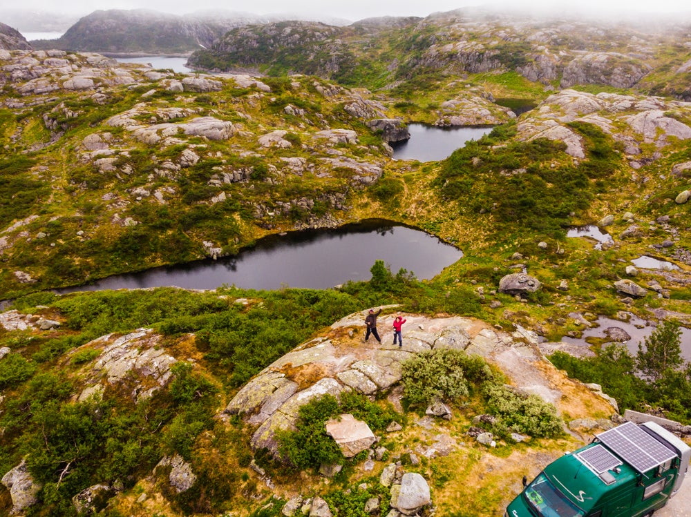 Aerial shot looking down on a couple in the backcountry beside a camping vehicle