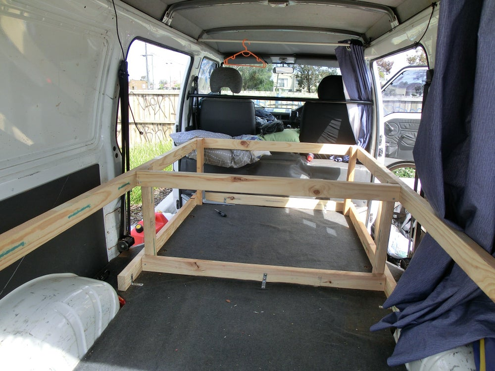 Wooden bed frame of 2x4s in a van