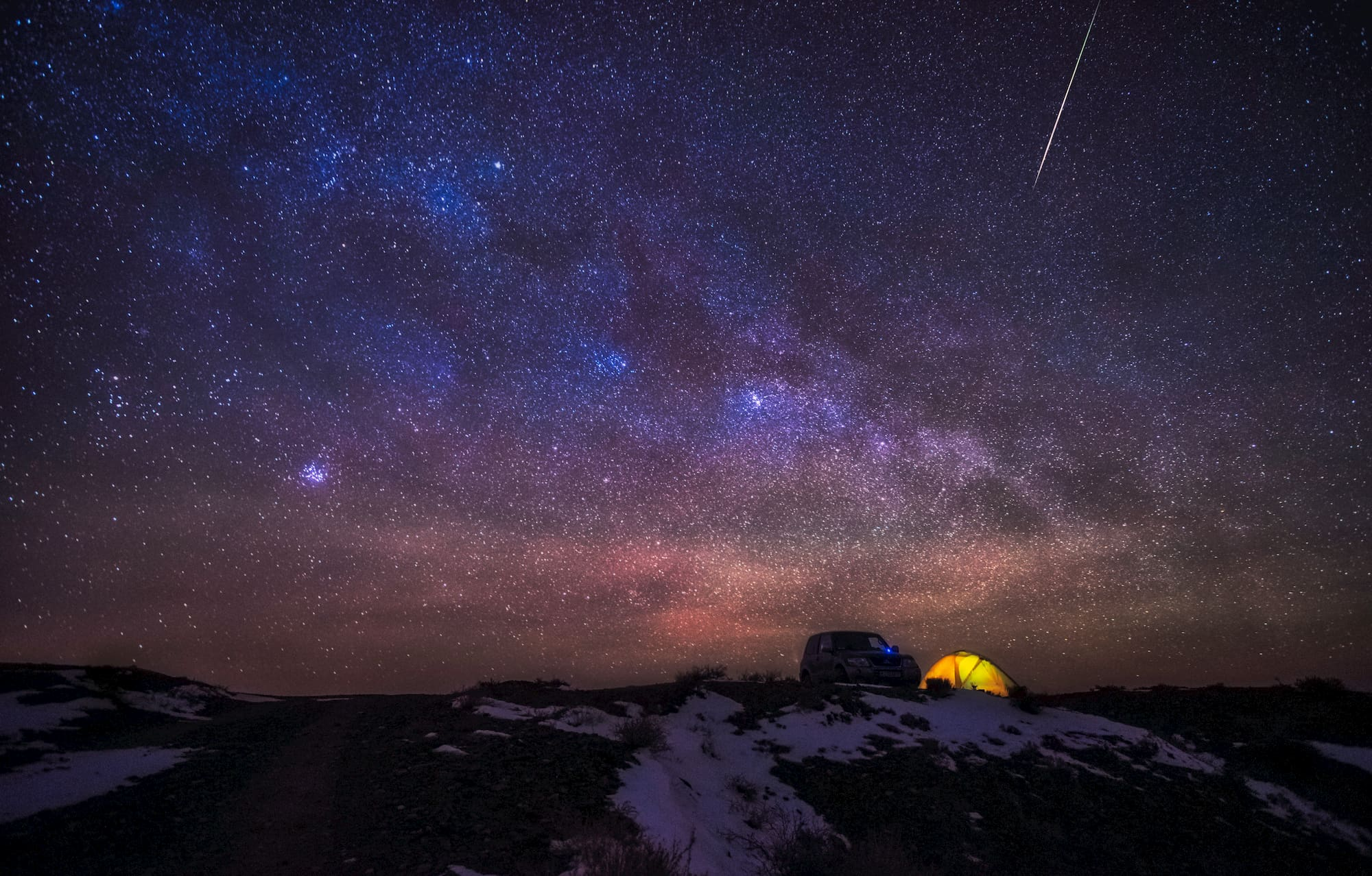 Yellow tent lit up under a purple night sky full of stars and a shooting star.