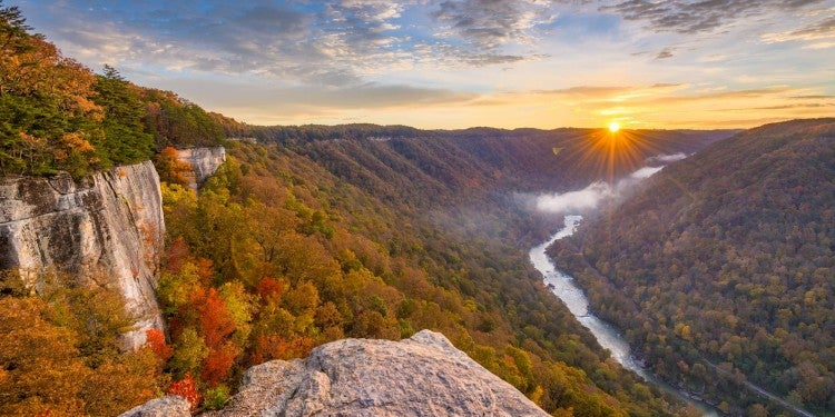 Panoramic view of the New River Gorge with boulder in foreground and sunset in background