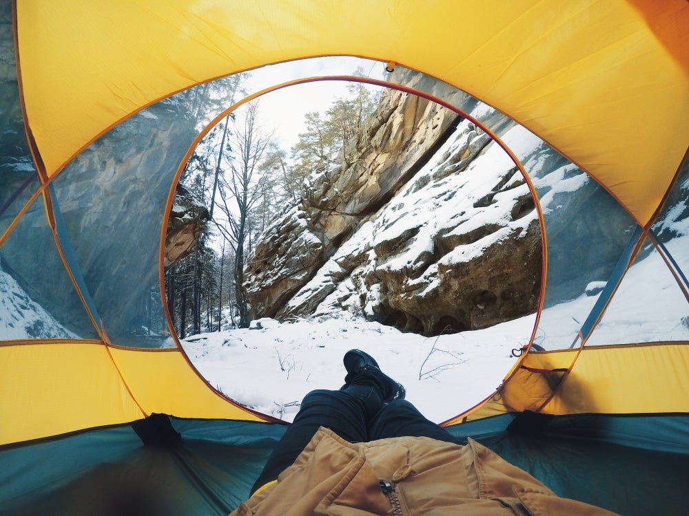 Camper resting on their back sticks feet out into snow through tent's circular opening