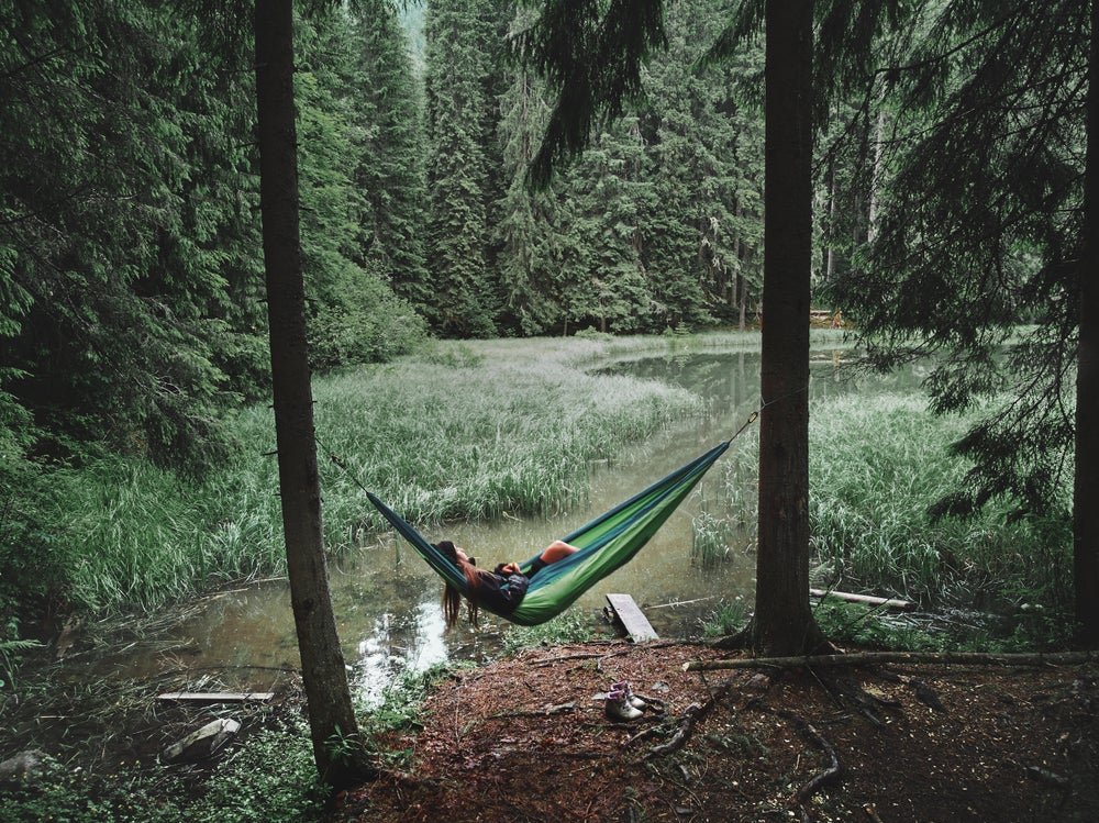 Woman sleeping in green hammock by a river in the forest.