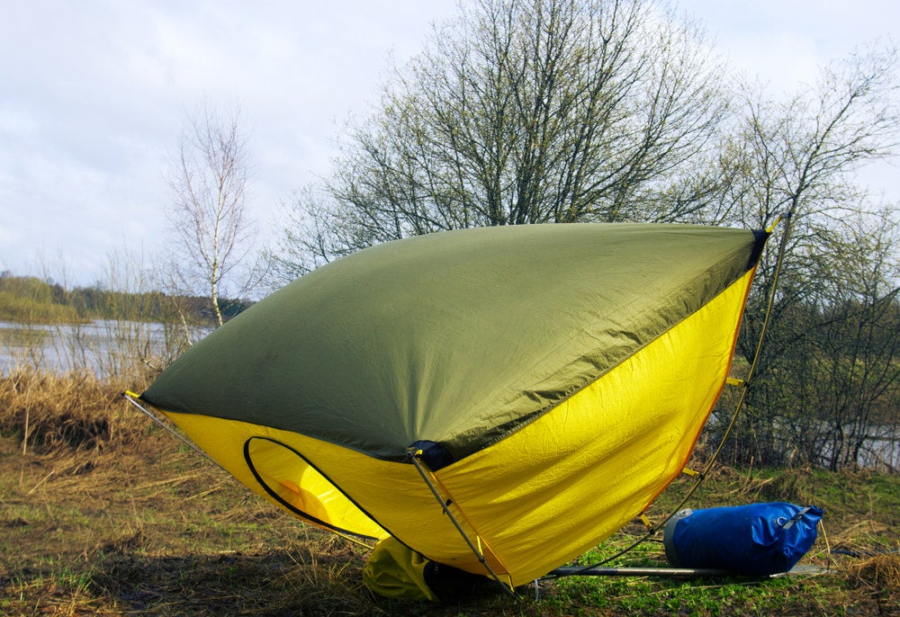 Windblown tent positioned upside down in a campsite.