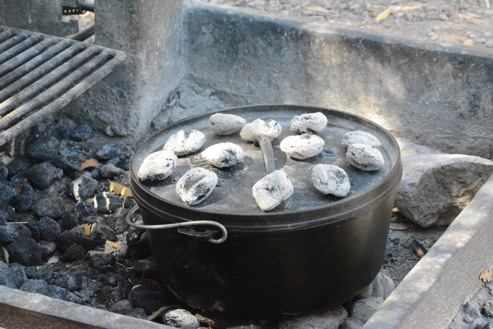 campfire cooking with dutch oven sitting on coals with coals on top of lid