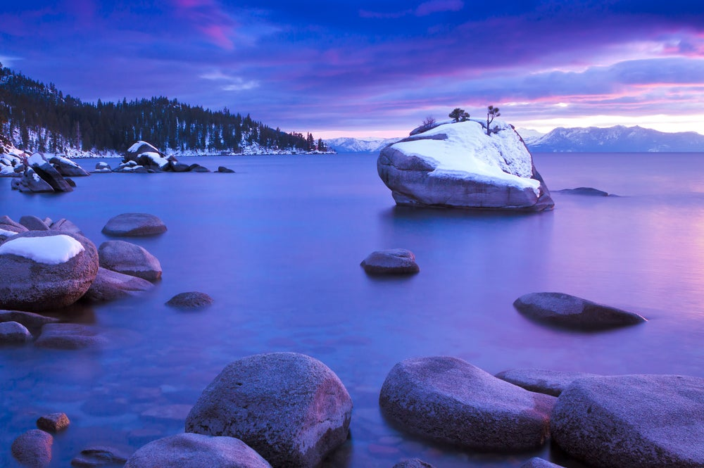 Pink sunlight of dusk shining on the snow capped rocks sticking out of Lake Tahoe.