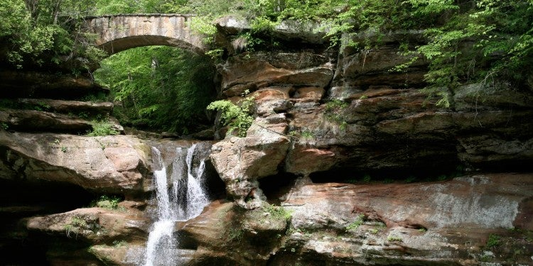 Waterfall rushing under the forested bridge in hocking hills state park