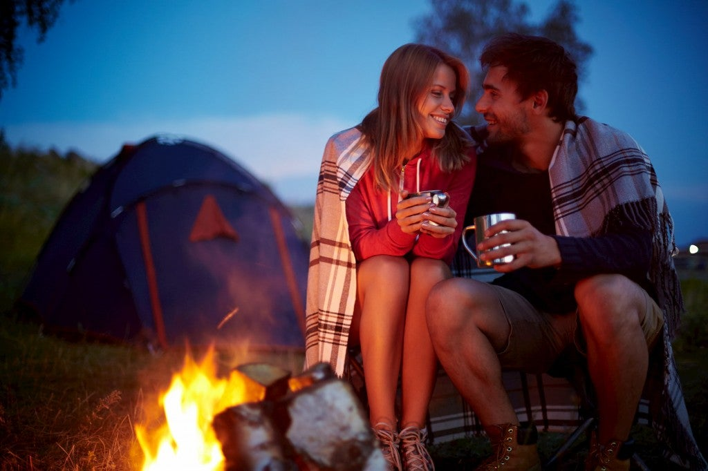 a couple sits close to a fire and eachother at night while camping