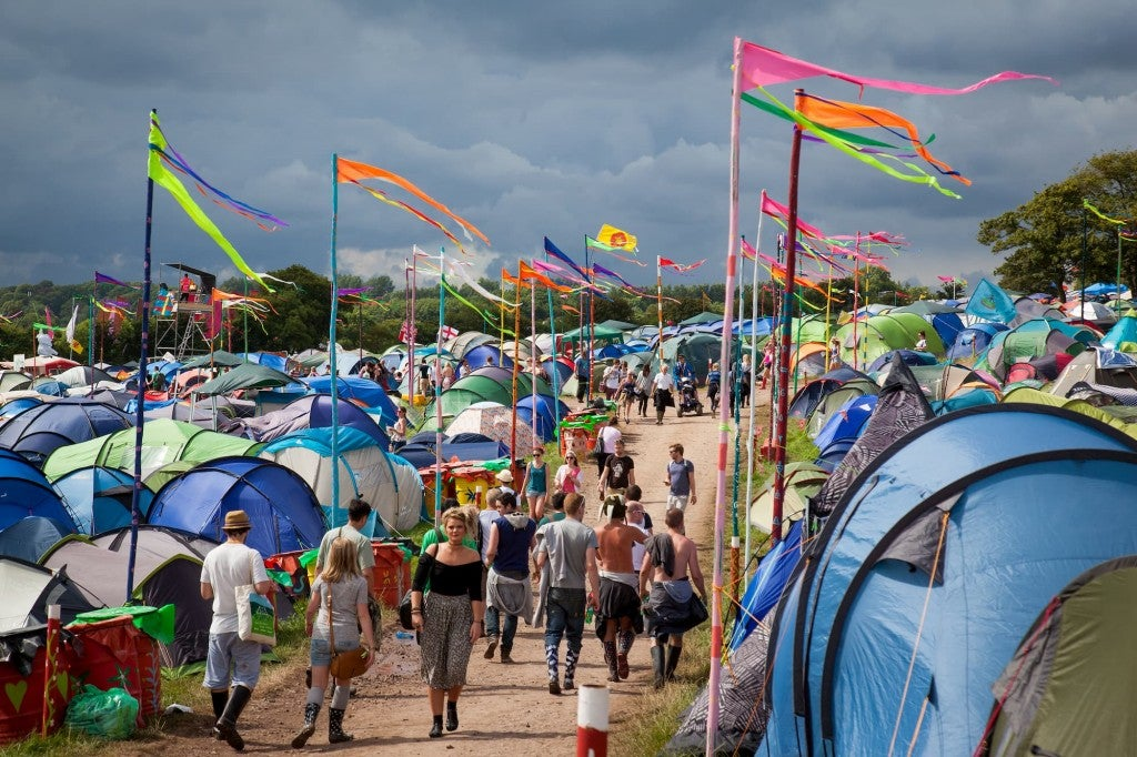 Groups of blue tents at a music festival with people walking along a path to the right
