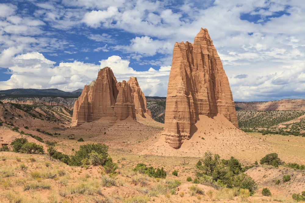 Red rock spires coming up from the ground with blue sky in background