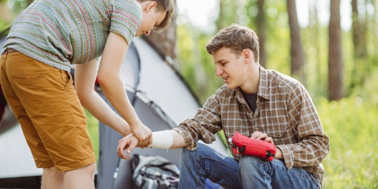 man uses a gauze wrap to properly bandage a friends wound at a camp site.