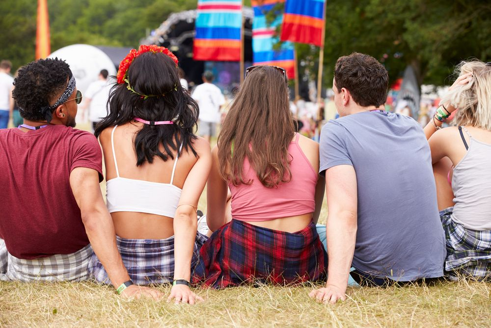 back view of five friends sitting on grass at a music festival