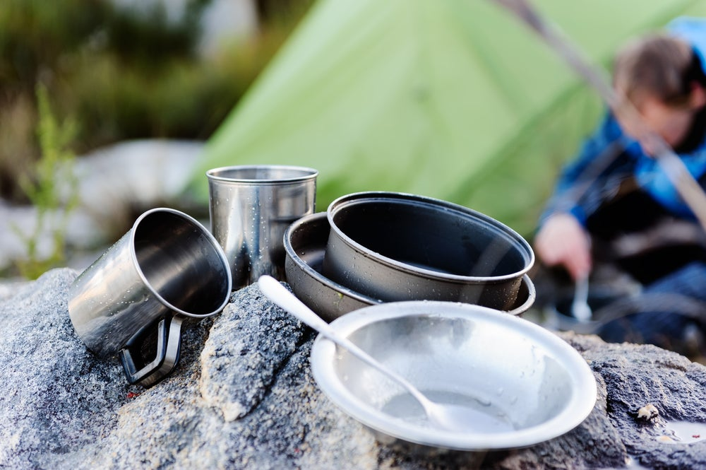 Camping mess kit and utensils resting on a rock after cleaning