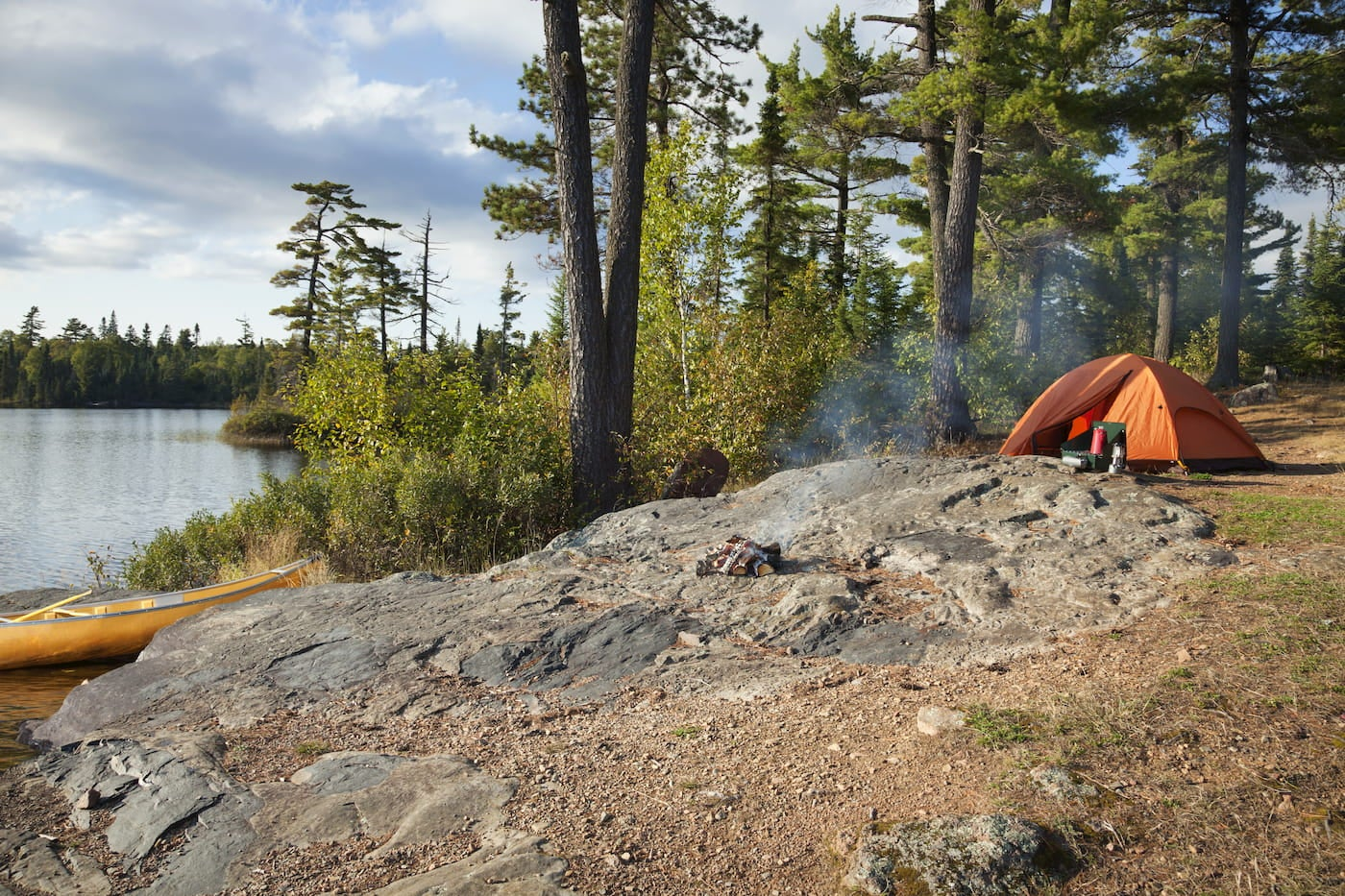 Tent set up on the rocks beside a lack where a canoe is hitched.
