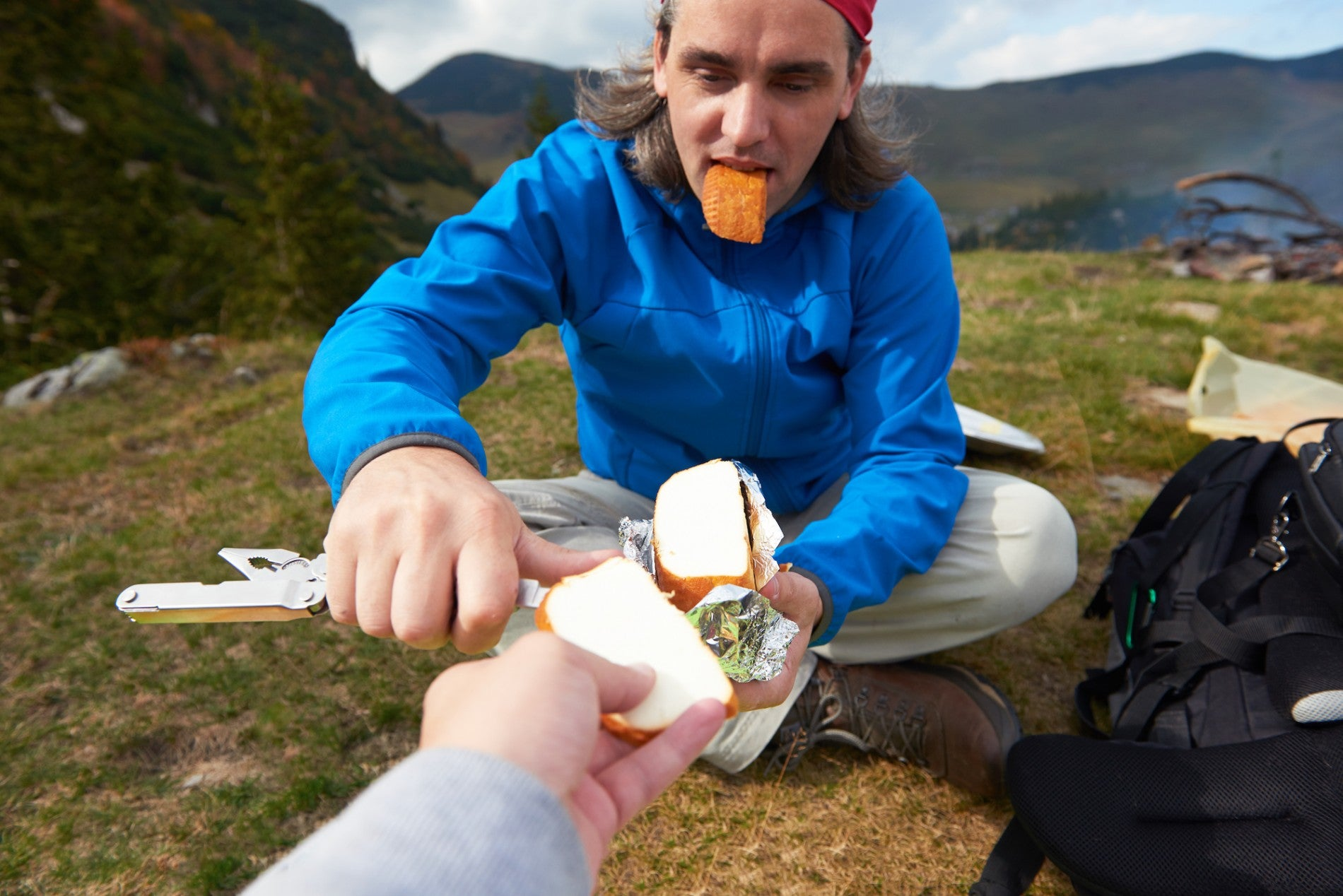 man slicing cheese held by photographer while seated in field