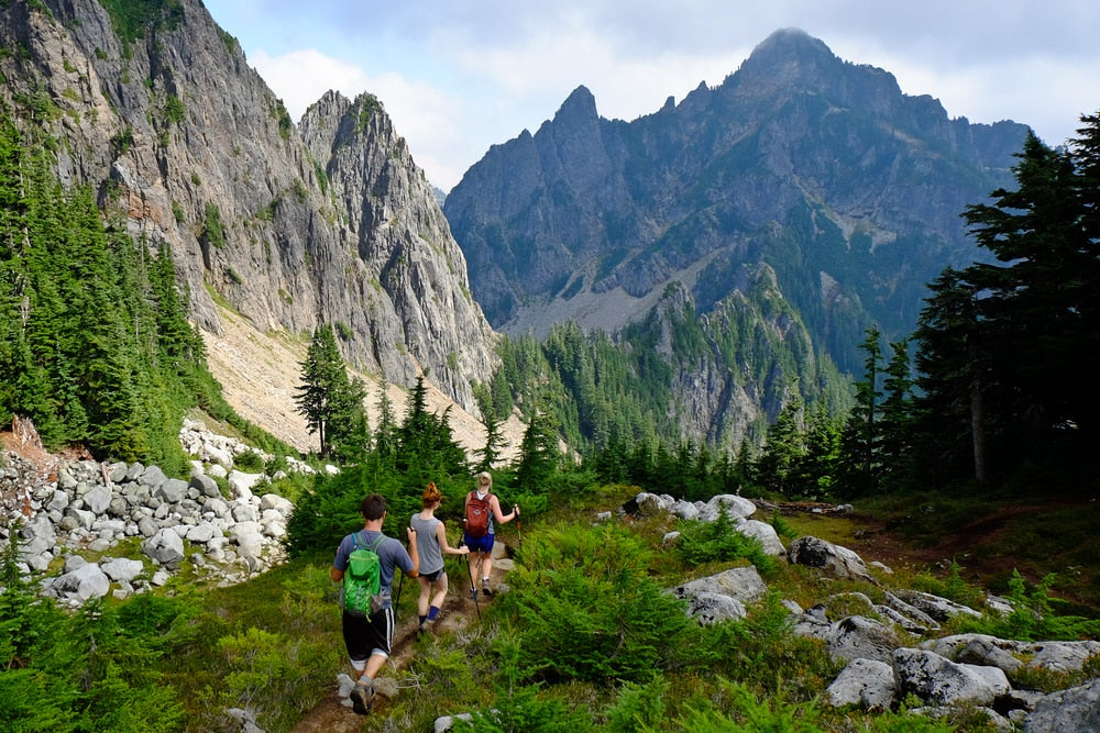 Three people backpacking on a trail with mountains in the background