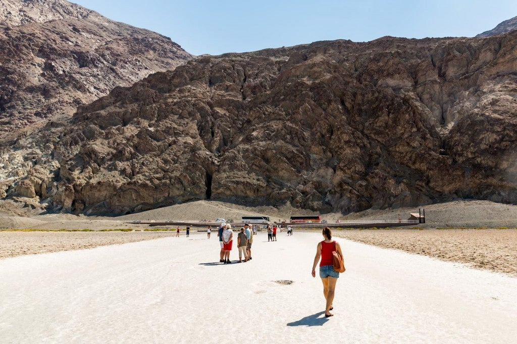 a woman walks toward a crowd and a mountain on a desert plain in death valley national park