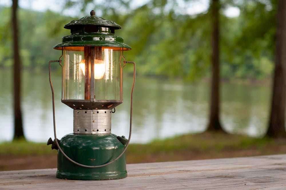 Propane lantern on picnic table with lake in background