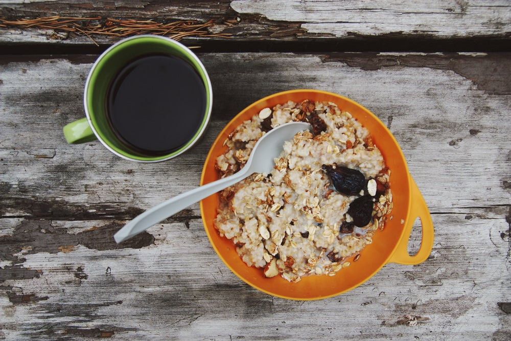 Bowl of oatmeal beside a mug of coffee on an aged wooden table