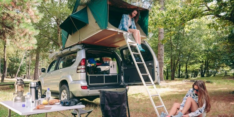 woman sits in rooftop car tent near ladder leading to her friend on the ground at a campsite