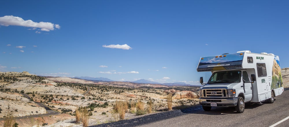 RV driving on highway 12 in utah in front of a dry desert