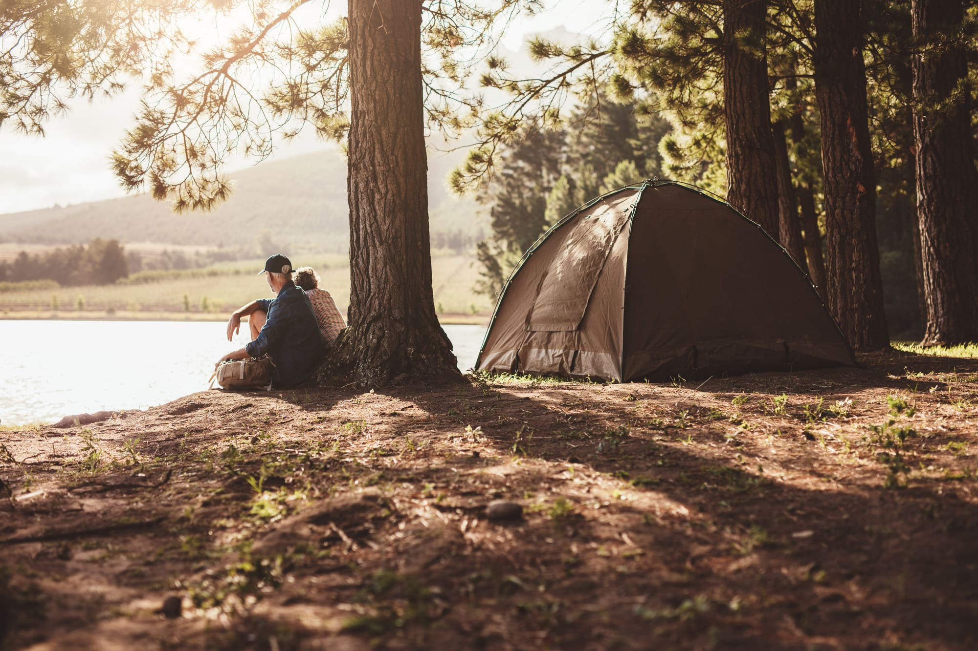 Couple sitting by the edge of a lake in the sun beside their tent