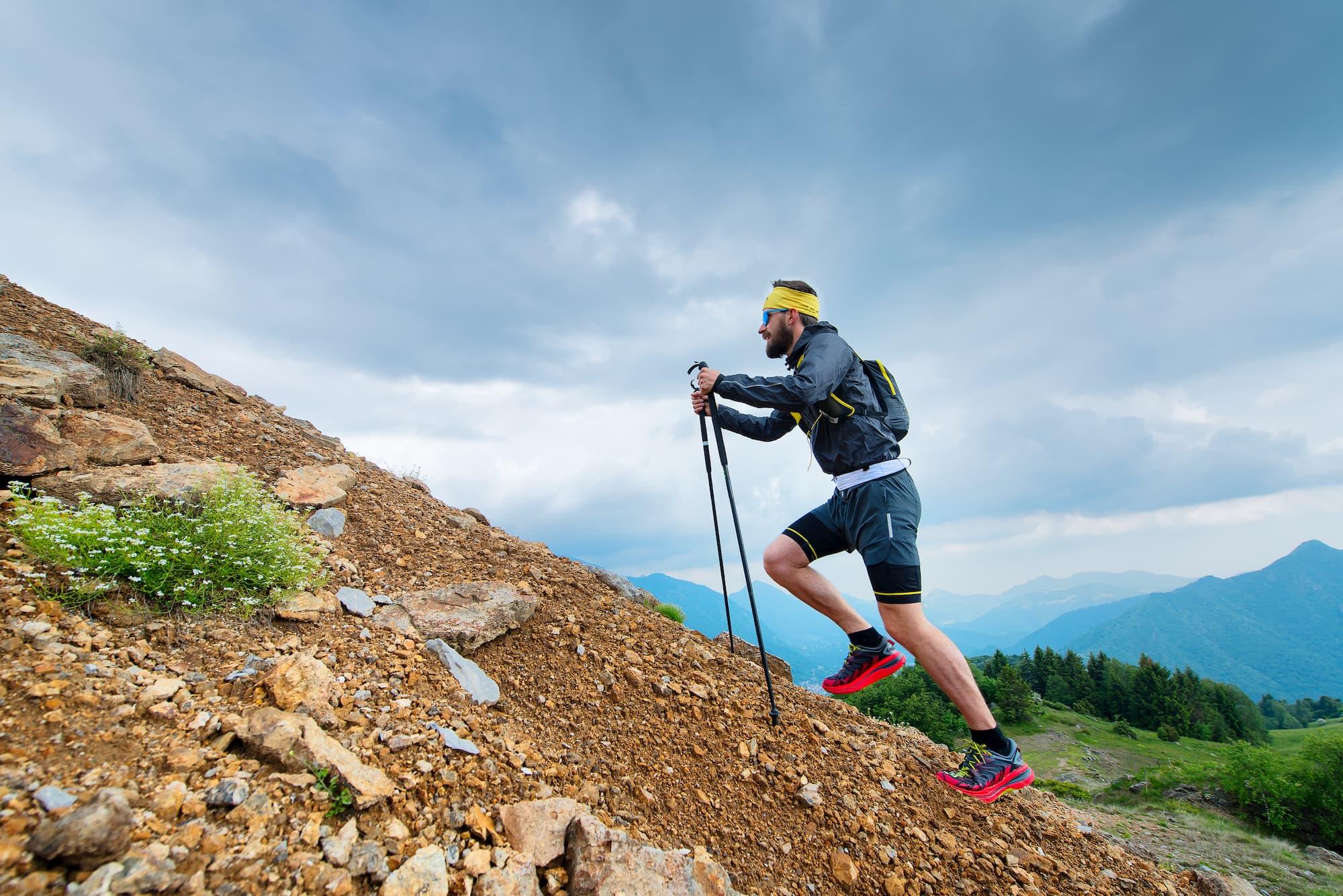 Man hiking uphill with trekking poles.