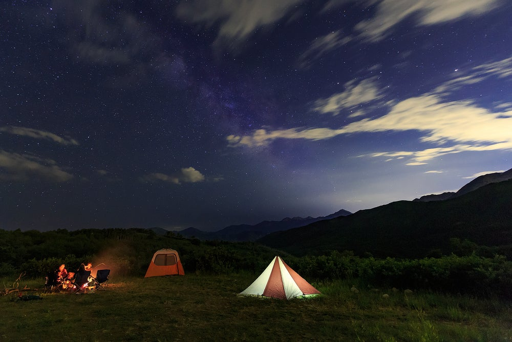 Tent and campfire set up at night within the Wasatch Mountain area of Northern Utah.