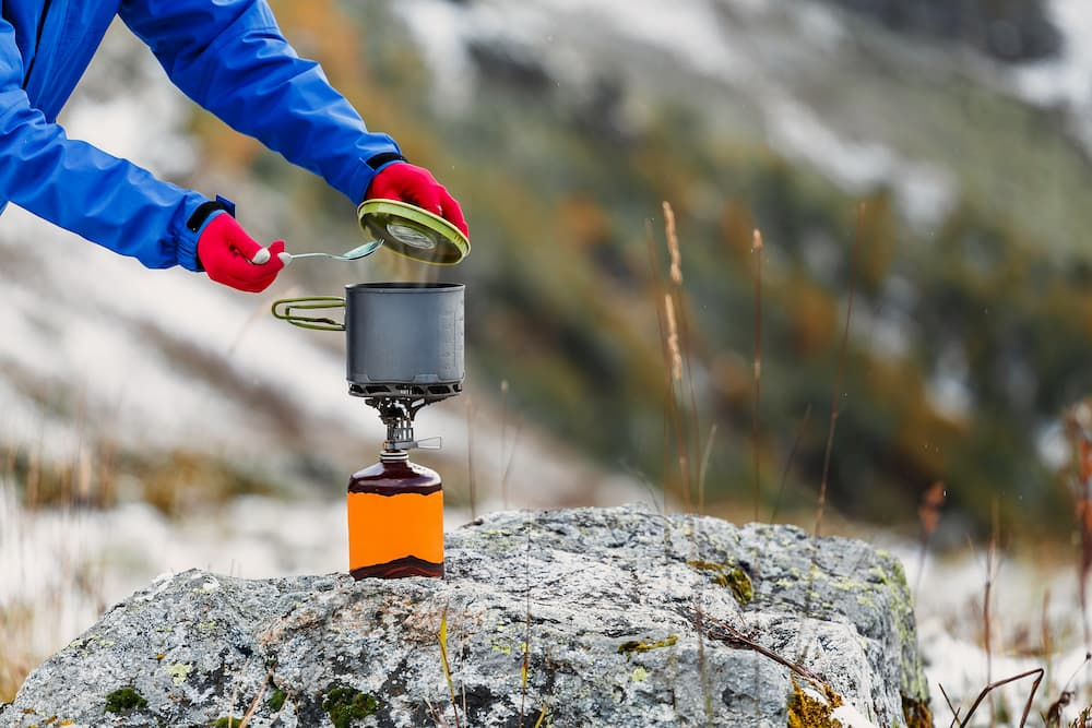 a camper checking on a meal cooking on a backpacking stove