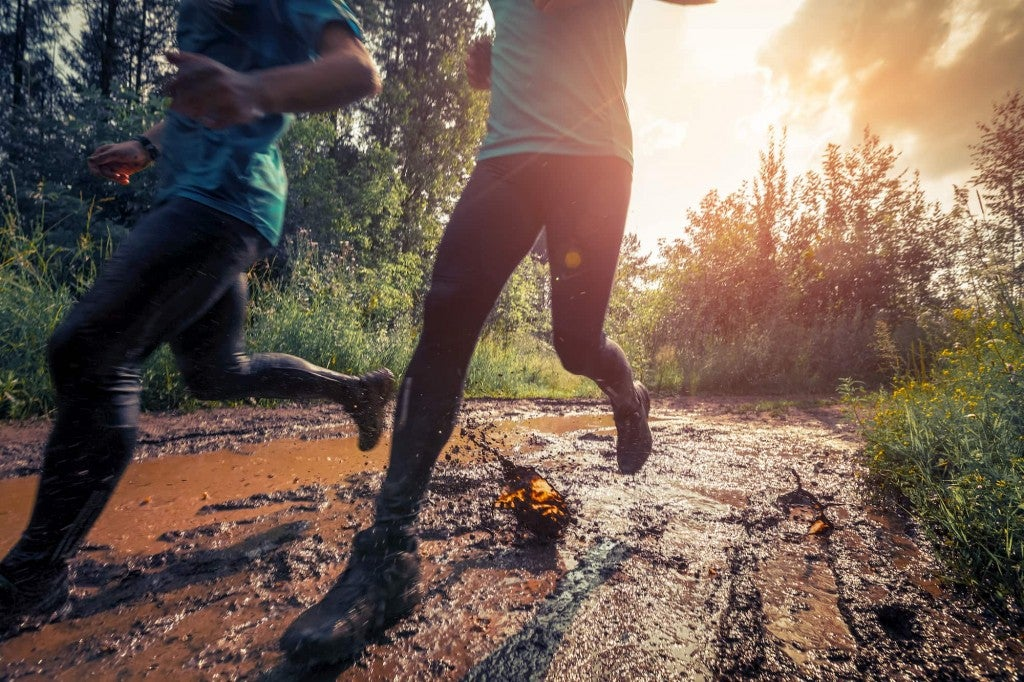 two runners on a muddy trail at sunset with the camera focused at their hiking and running shoes