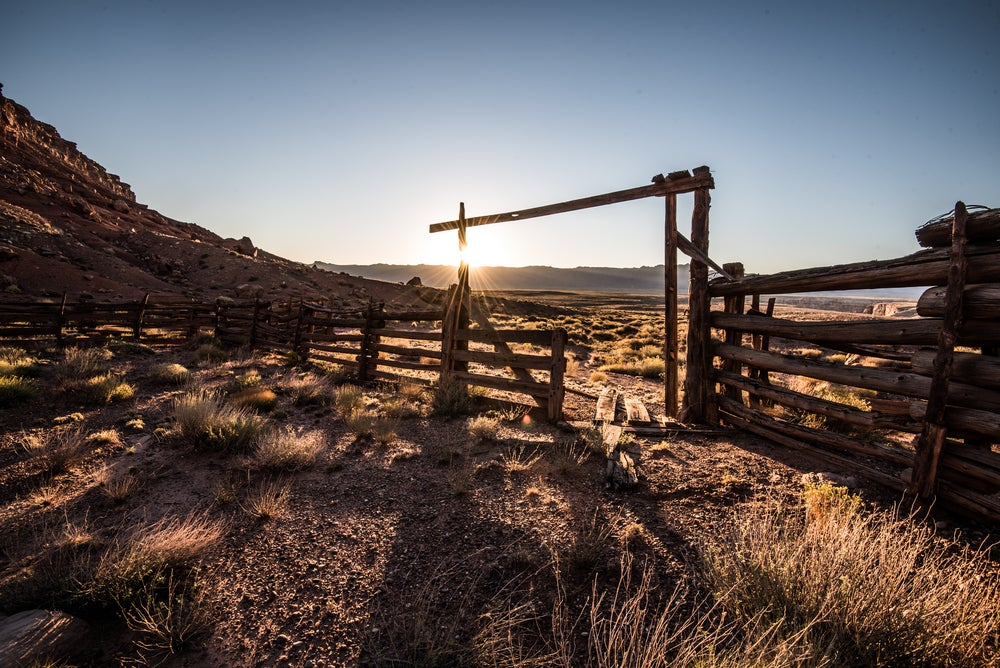 Low sun casts long shadows from wooden dude ranch fencing in arizona farm