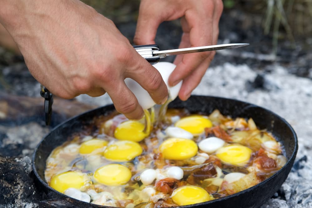 a person cracking eggs in cast iron skillet over campfire coals