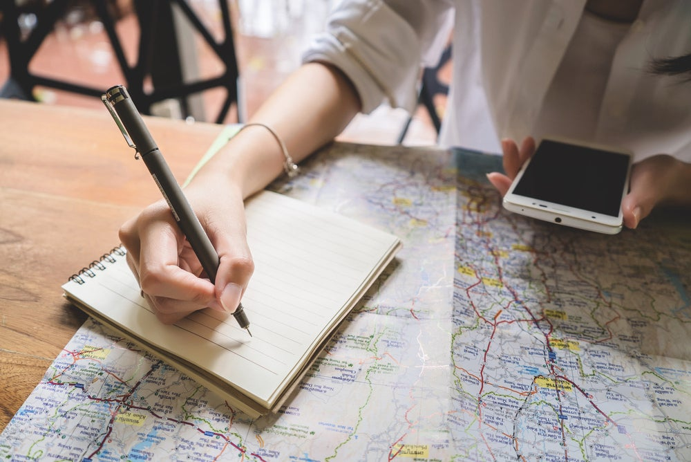 Woman looking at map and writing in notebook with phone in her hand