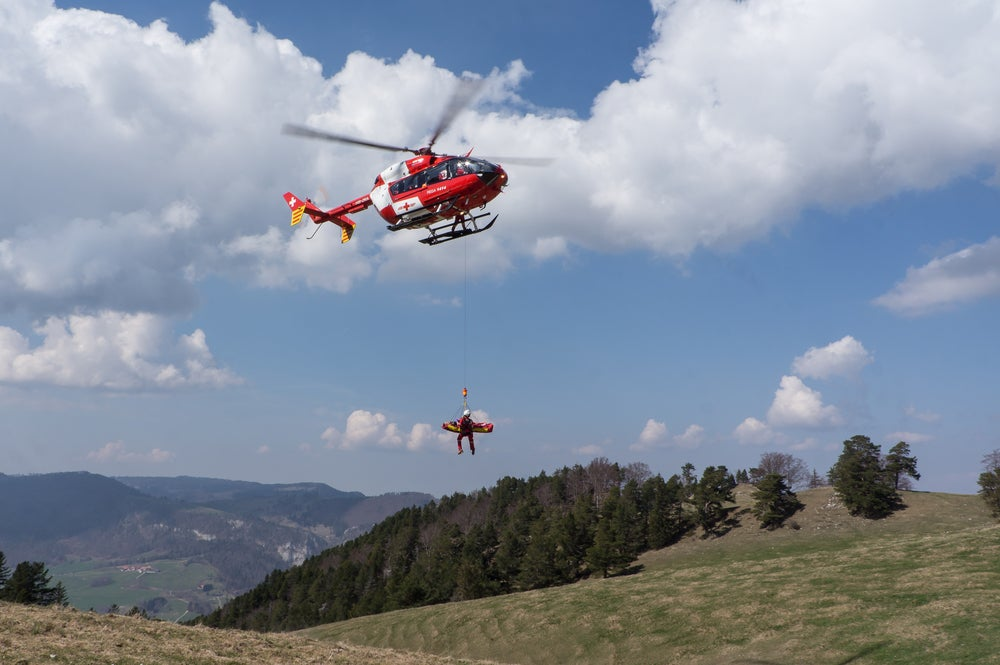 Injured person on a stretcher gets airlifted by a helicopter out of the back country.