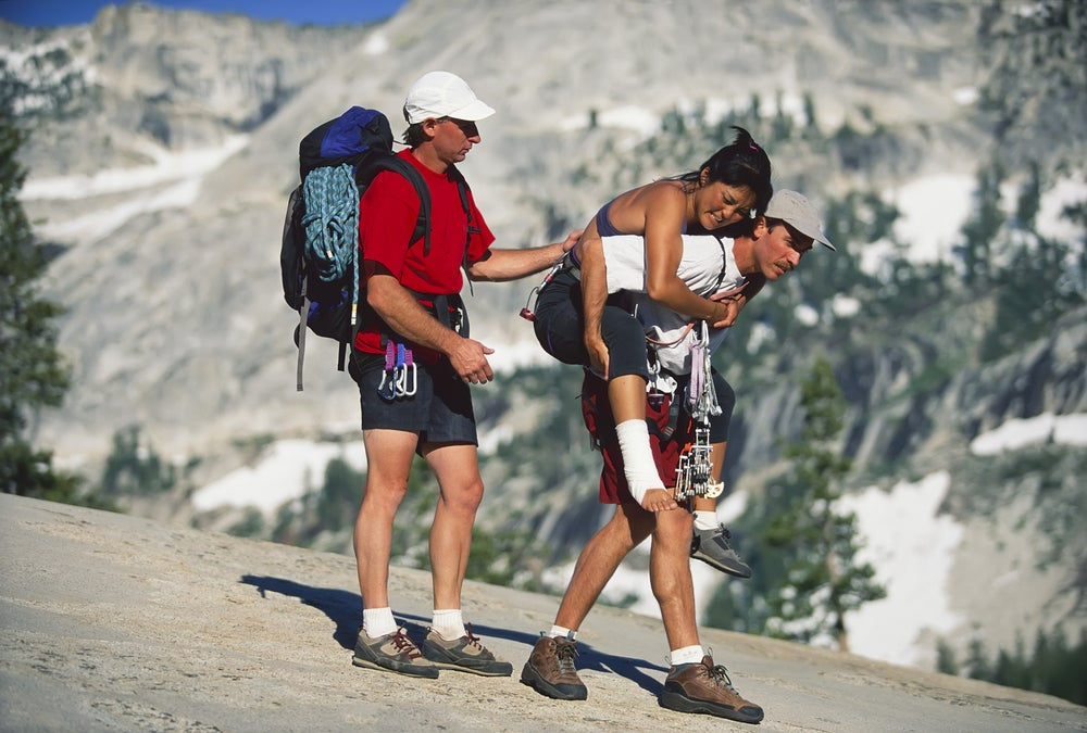 Two guys carry out an injured female climber wearing an ankle bandage on a mountainside.