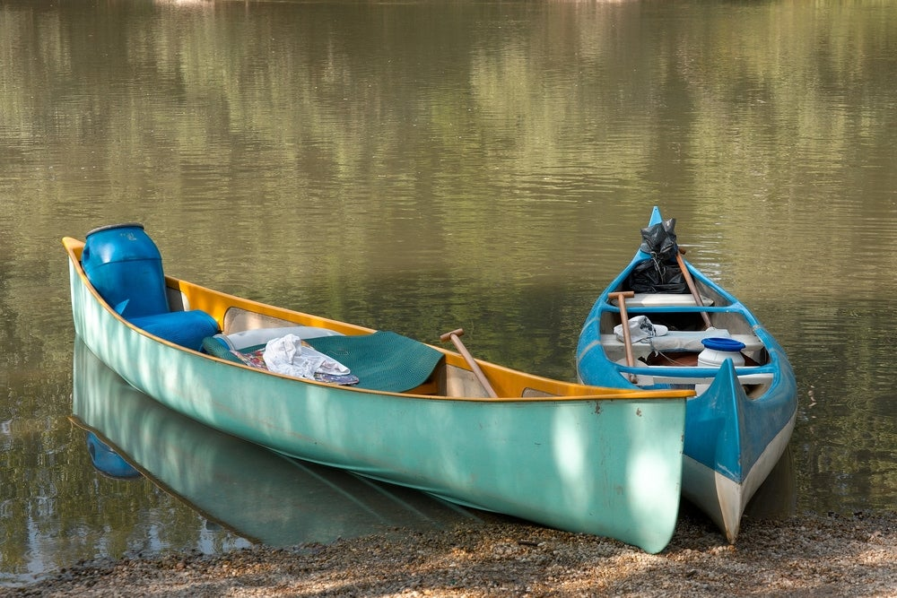 Tied up canoes filled with camping gear.