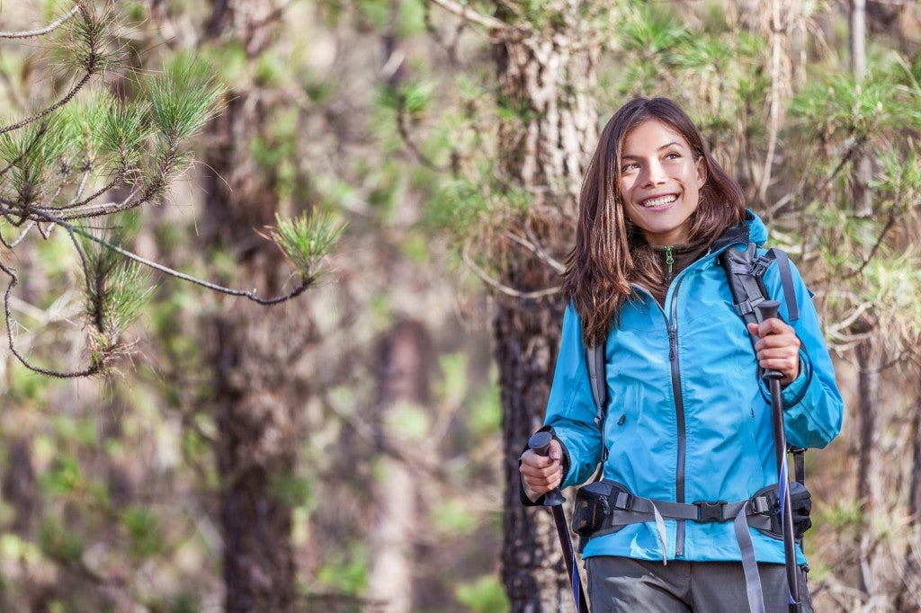 Woman hiking and smiling with trees in background