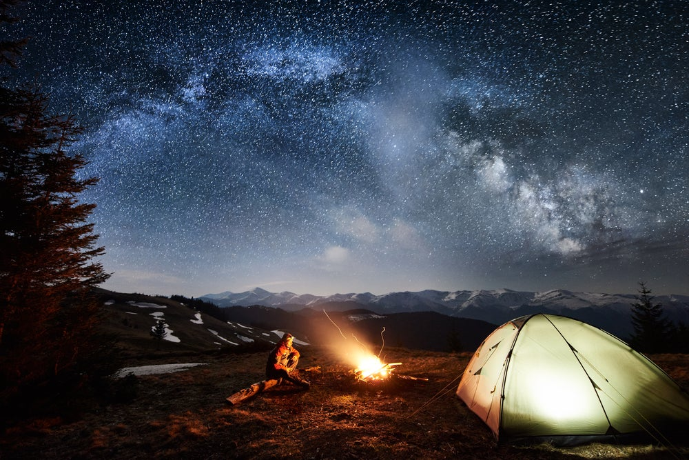 Long exposure of lone camper sitting fireside below stars and beside illuminated tent