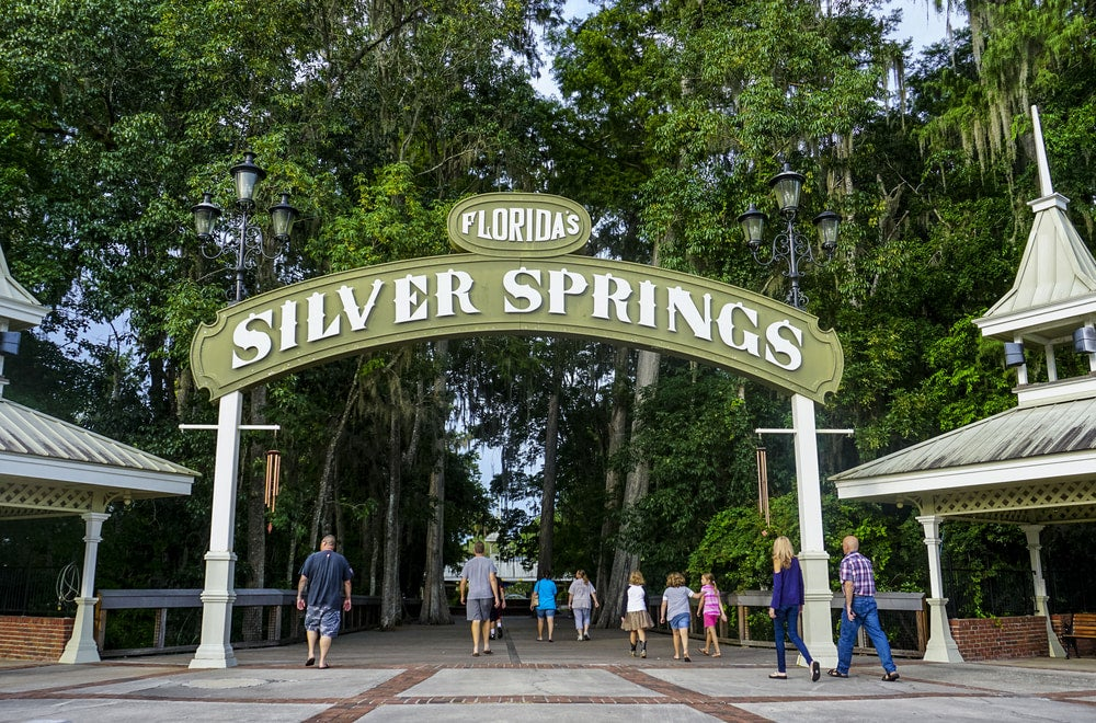 """An arched sign saying """"Florida's Silver Springs"""" with people walking through archway"""