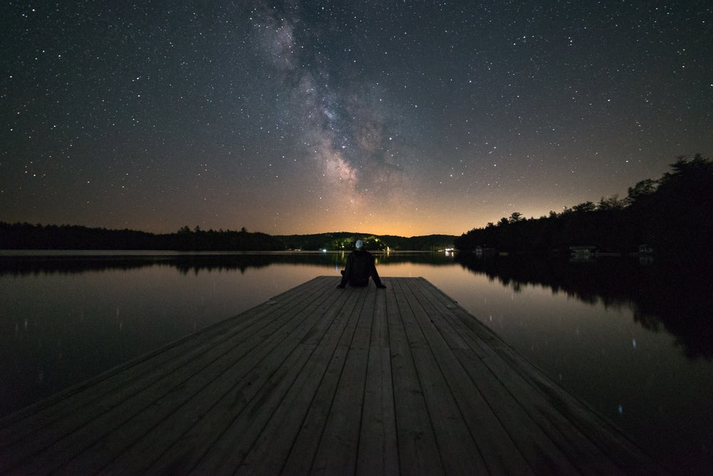 Man lounging on a dock at dusk under the stars.