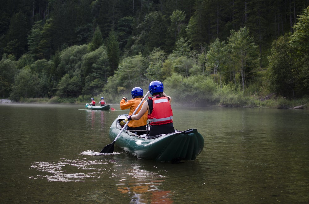 two people in helmets and vests paddling down a river in an inflatable canoe.