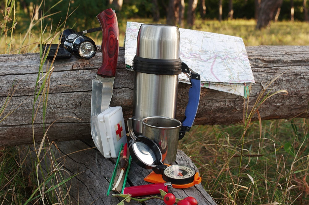 A knife, first aid kit, headlamp, compass placed on a log.
