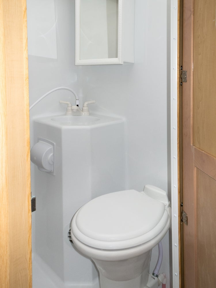 Traditional plastic rv toilet in a white plastic bathroom.