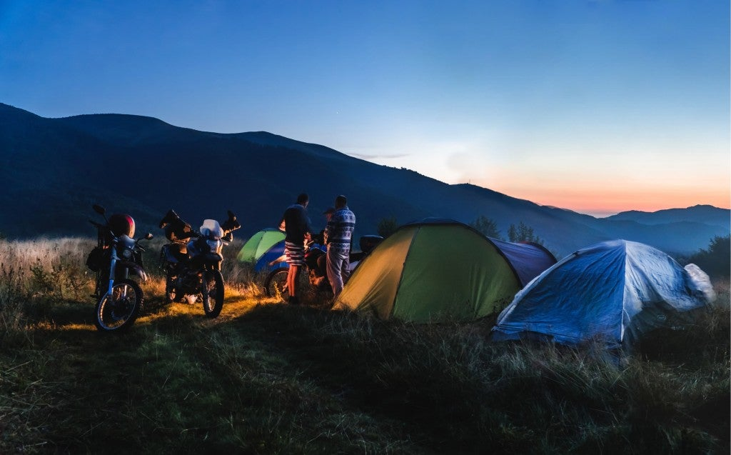 sunset at a mountain campsite with tents and dual sport motorbikes
